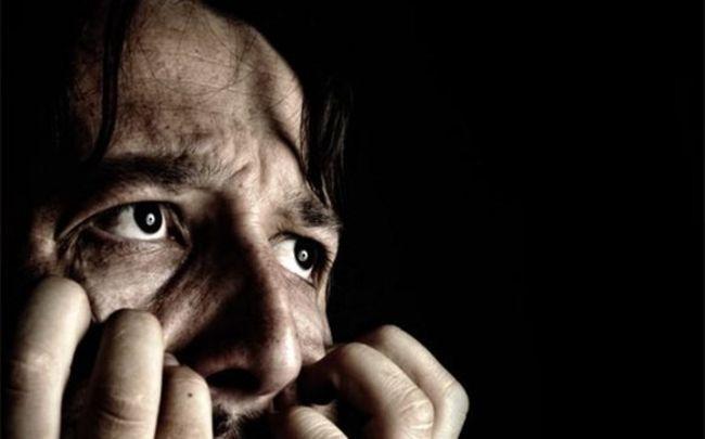 Мужчина шизофреник на черном фоне