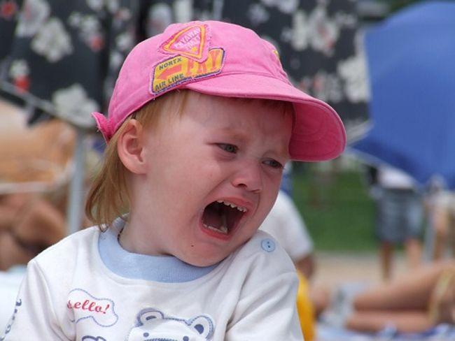 ревет малыш в розовой кепке