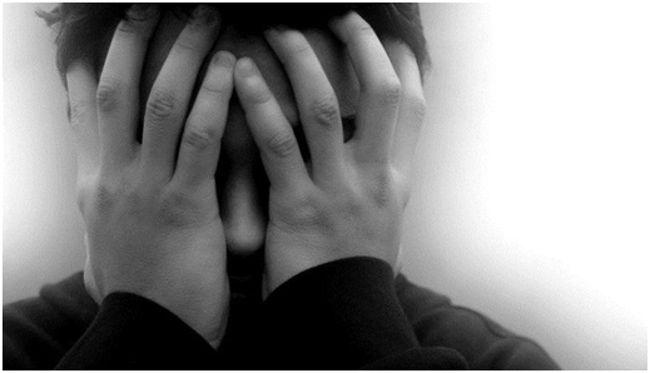 мужчина закрывает лицо руками
