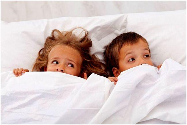 девочка и мальчик прячутся под одеялом