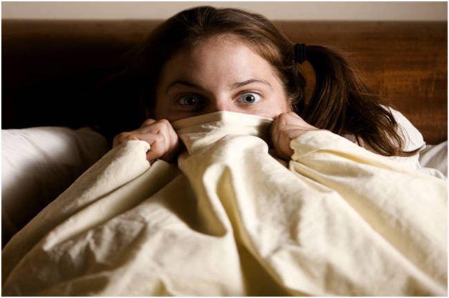 девушка прячется под одеялом