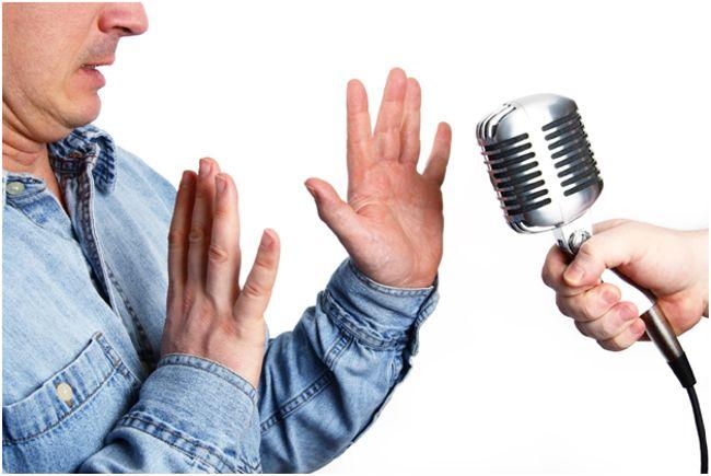 мужчина отталкивает микрофон
