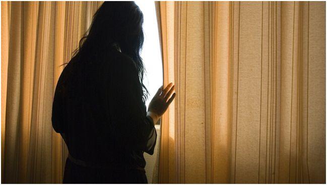 женщина, смотрящая из окна на улицу
