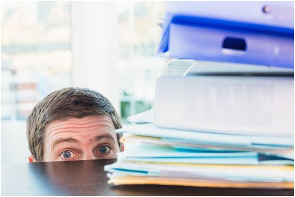 мужчина прячется за рабочим столом